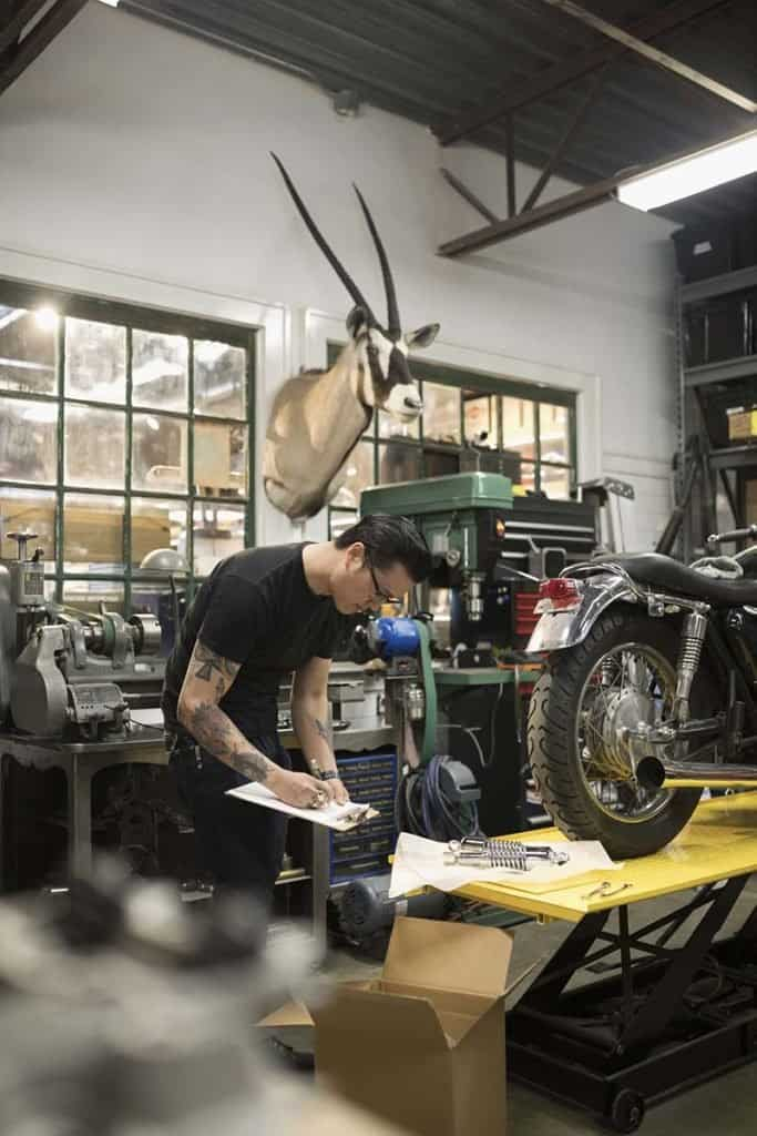 Motorcycle mechanic with clipboard checking inventory in auto repair shop