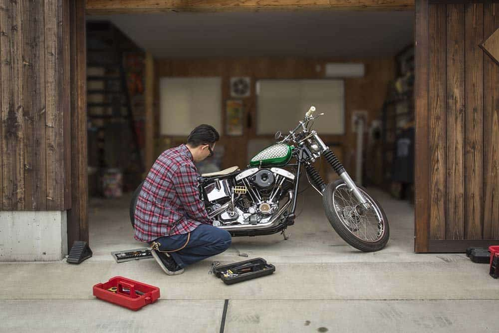 A man repairing his motorcycle in his garage